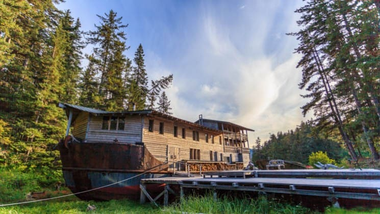 A boardwalk leads to a boat house on the water and next to tall pine trees at the Tutka Bay Wilderness Lodge in Alaska