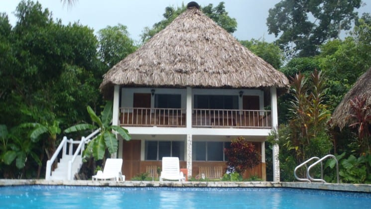 The main building at the Tikal Inn, a bungalow with a thatched roof, swimming pool, and lounge chairs.