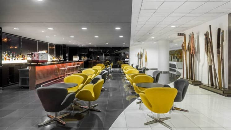 Modern yellow chairs are situated near small tables in the bar and lounge area of the Wyndham Costa del Sol hotel, connected to the Lima International Airport
