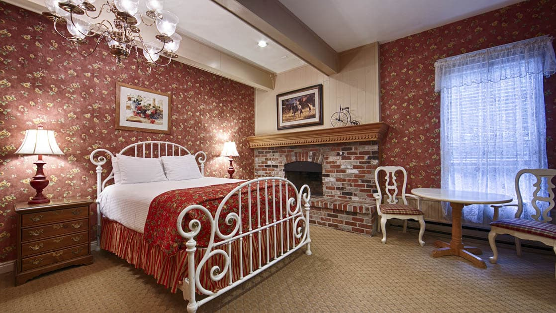 A room with a metal Victorian-style bed frame, red linens, a brick fireplace, and a chair at the Best Western Grandma's Feather Bed Hotel in Juneau, Alaska