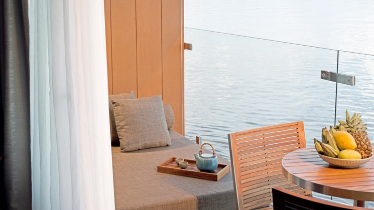 Aqua Mekong Design Suite Balcony with chair, table and fruit platter.