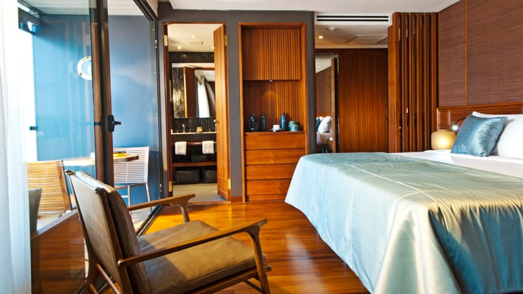 Aqua Mekong Design Suite with Balcony, floor to ceiling windows, chair and Double bed Set Up.
