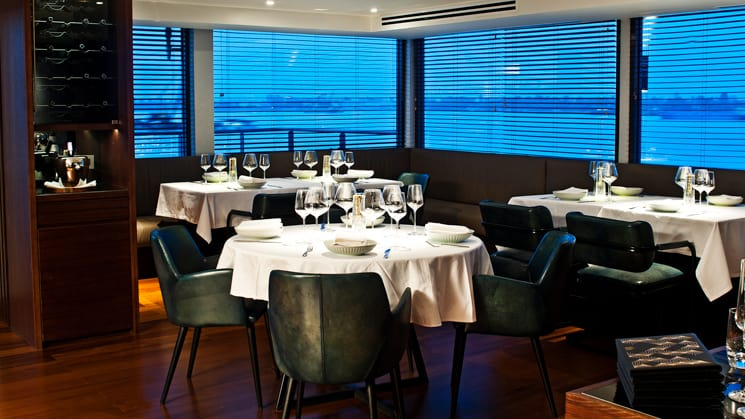 Aqua Mekong Dining Room with white table clothes, black chairs and large windows.
