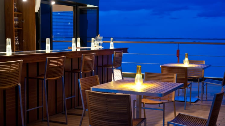 Aqua Mekong Outdoor Bar with bartop, small tables and candles.