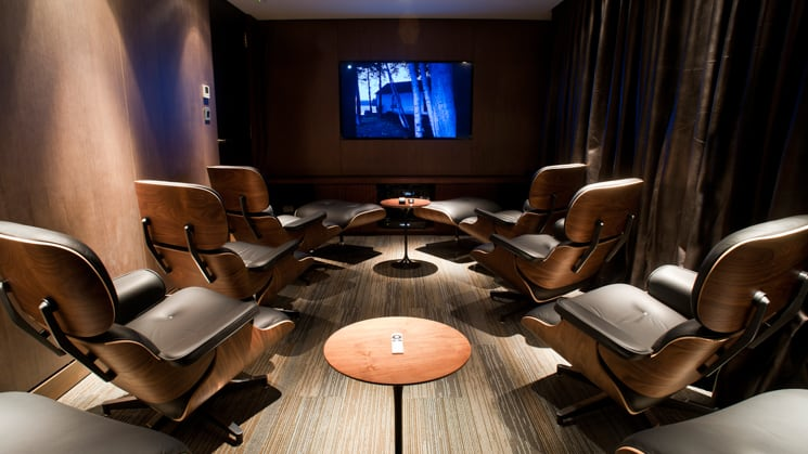 Aqua Mekong indoor Cinema with large screen and comfortable chairs in a small, dark room
