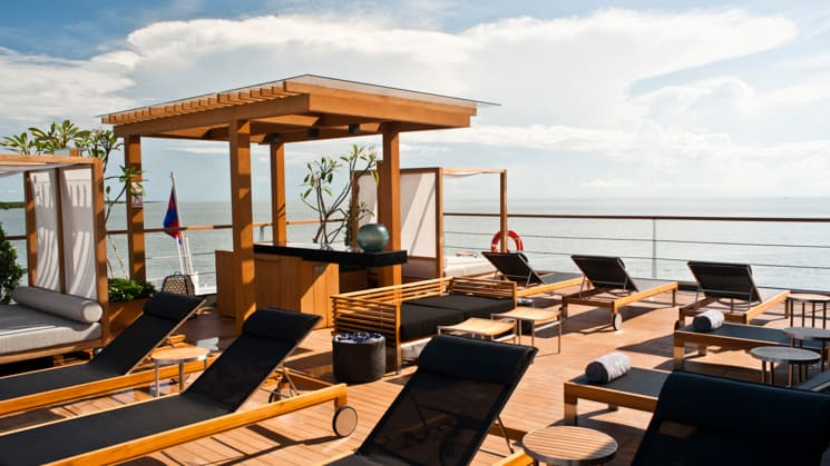 Aqua Mekong Sun Deck with black chaise lounges, wood deck and view of river.