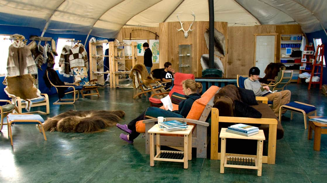 Arctic Watch large group tent with chairs and couches full of people hanging out.