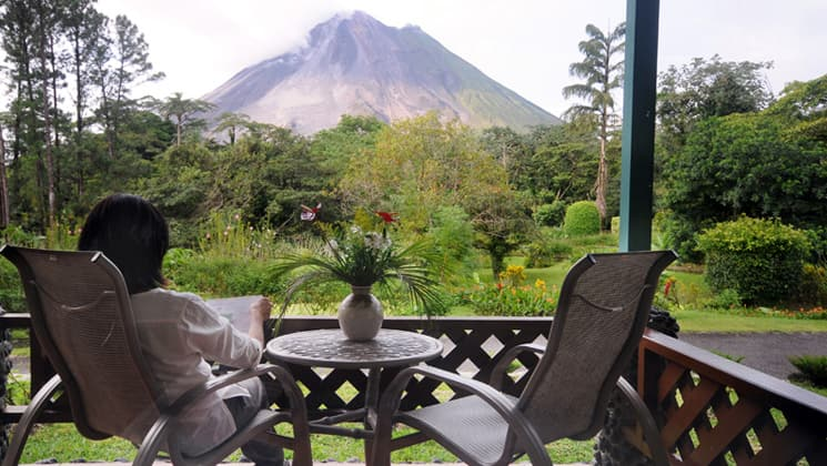 Woman sitting on private balcony of Smithsonian Room at Arenal Observatory Lodge in Costa Rica
