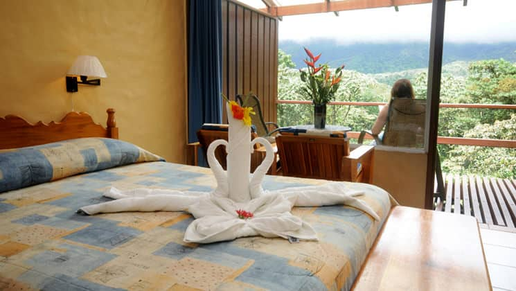 Smithsonian Room with one bed and guest sitting on private deck at Arenal Observatory Lodge in Costa Rica