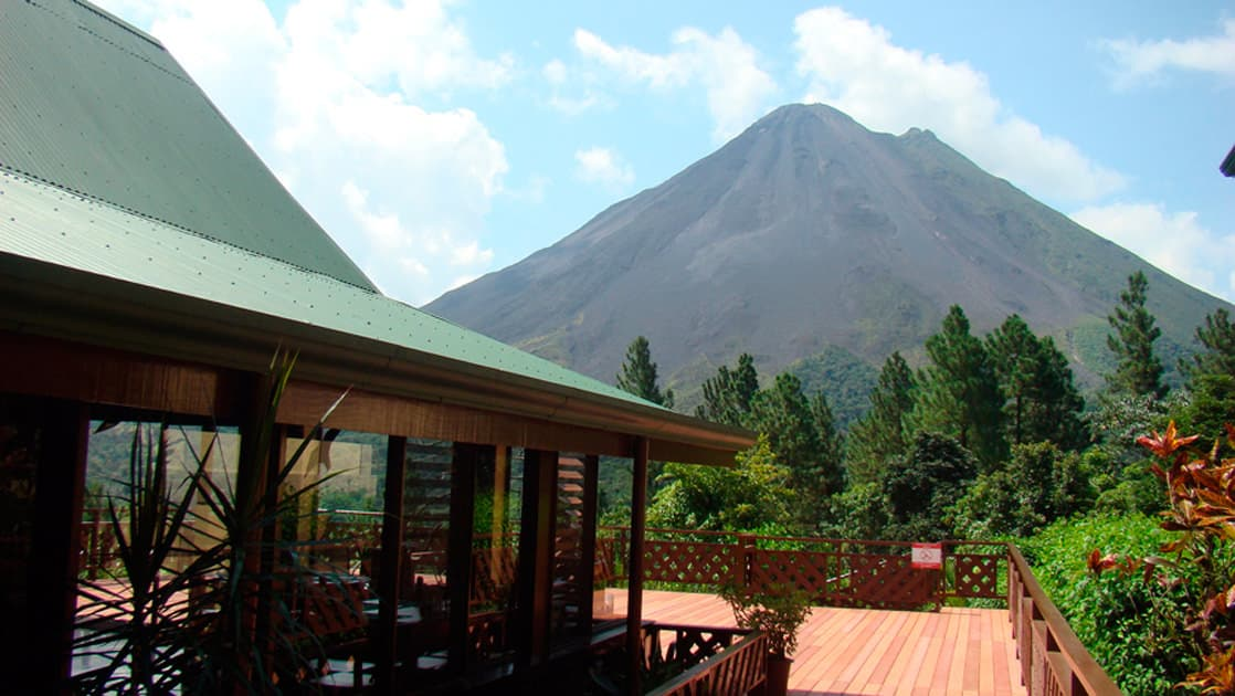 Sunny deck of main lodge at Arenal Observatory Costa Rica Lodge with Arenal Volcano in background