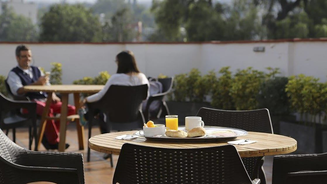 Breakfast with orange juice, fruit, and fresh bread is served on a table in an outdoor courtyard, where people are enjoying the morning buffet at the Casa Andina Standard Arequipa in Peru.