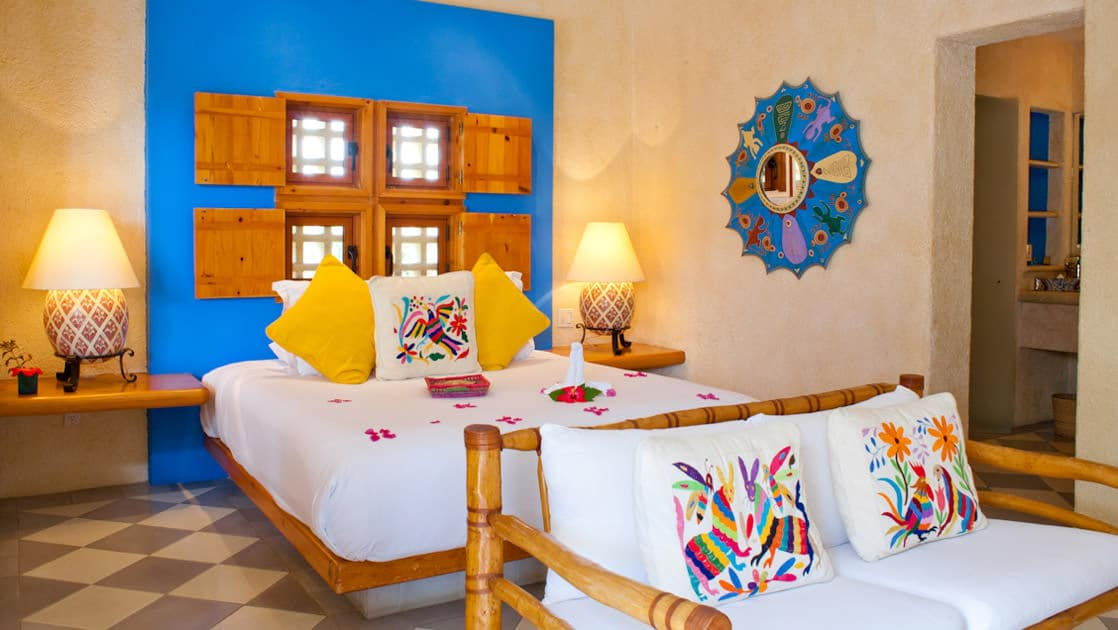 Large bed covered in red flower petals and colorful pillows, with loveseat and Mexican-style artisan wall hangings at Casa Natalia in San Jose del Cabo on the Baja Peninsula