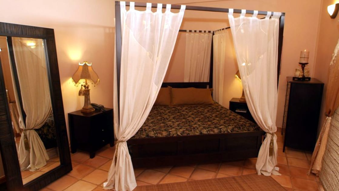 Canopy bed and large mirror in bedroom of Chabil Mar Villas in Belize