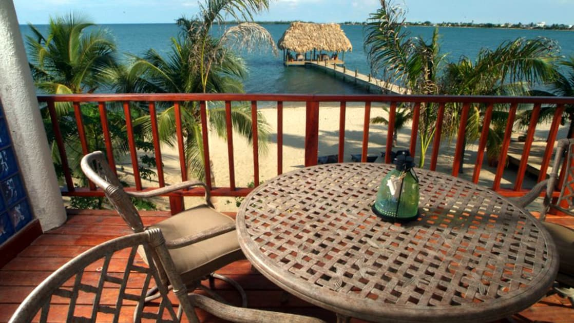 Private dining patio with table and chairs for four, plus vast beach and ocean view at Chabil Mar Villas in Belize