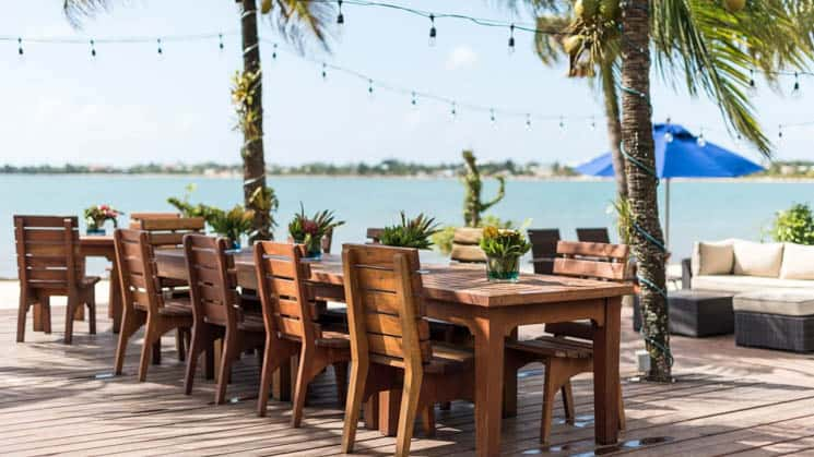 Beachfront wooden dining table with seating for nine at Chabil Mar Villas in Belize