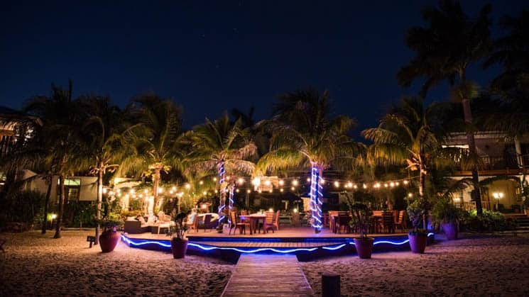 Beachside dining area at night, illuminated by white and blue lights at Chabil Mar Villas in Belize