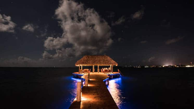 The dock at Chabil Mar Villas in Belize, surrounded by water and illuminated from below at night with blue lights