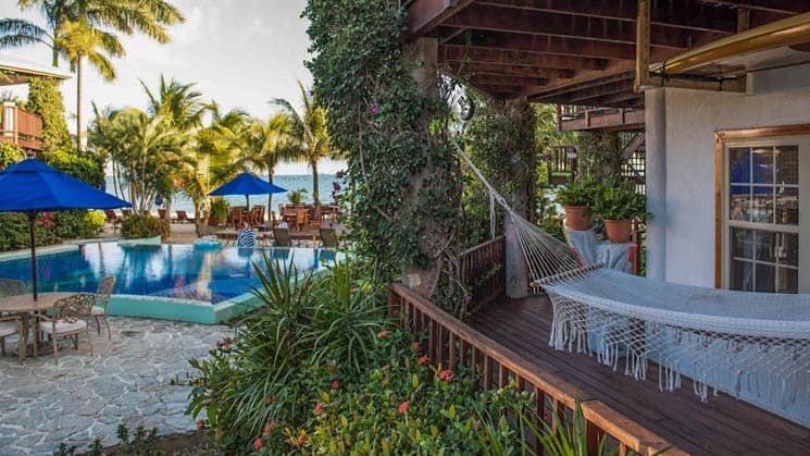 Private deck with hammock near pool and seaside dining area at Chabil Mar Villas in Belize