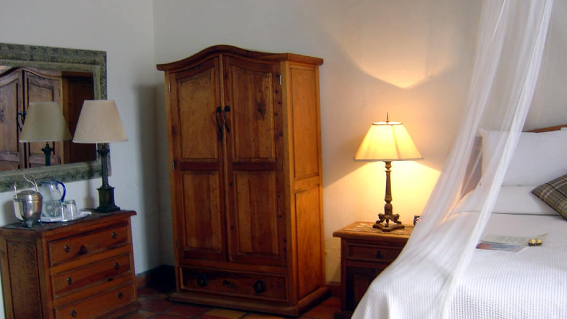 Inside a room, with a mosquito net draped over a queen-sized bed, an armoire, and handcrafted furniture at Todos Santos Inn, an old hacienda hotel in Baja