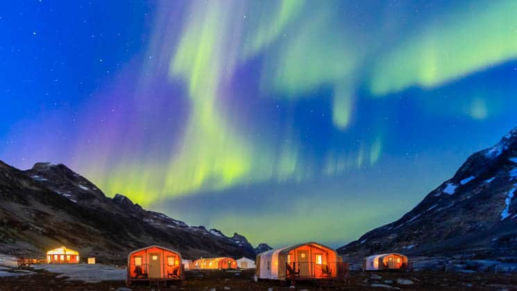 A glimpse of the Northern Lights, with green and purple colors, over lit-up cabins at Base Camp Greenland in Semerlik Fjord