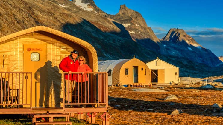 A man and a woman on the balcony of a private cabin at Base Camp Greenland, a refuge in the Arctic