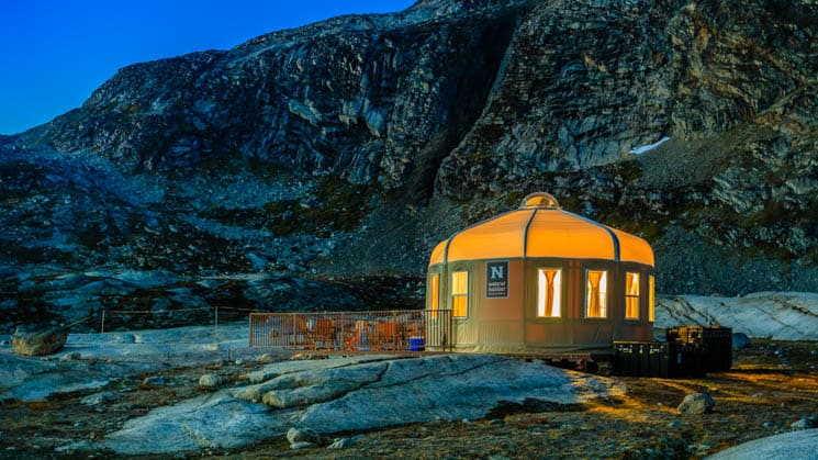 A lit-up yurt on the rocky bluff at Base Camp Greenland, in Sermilik Fjord