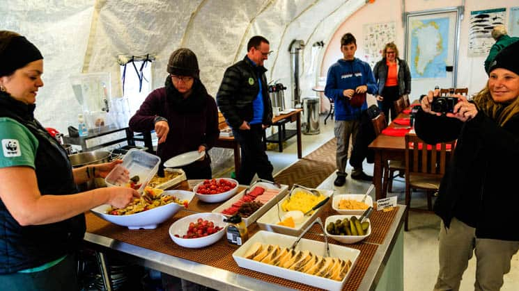 A woman is serving dinner with fresh ingredients to guests, buffet-style, at Base Camp Greenland in Sermilik Fjord