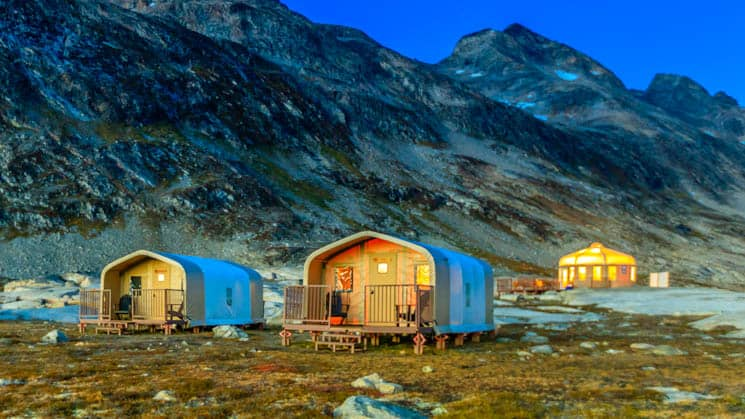 Two private cabins and the yurt at Base Camp Greenland, situated on a rocky bluff in Sermilik Fjord