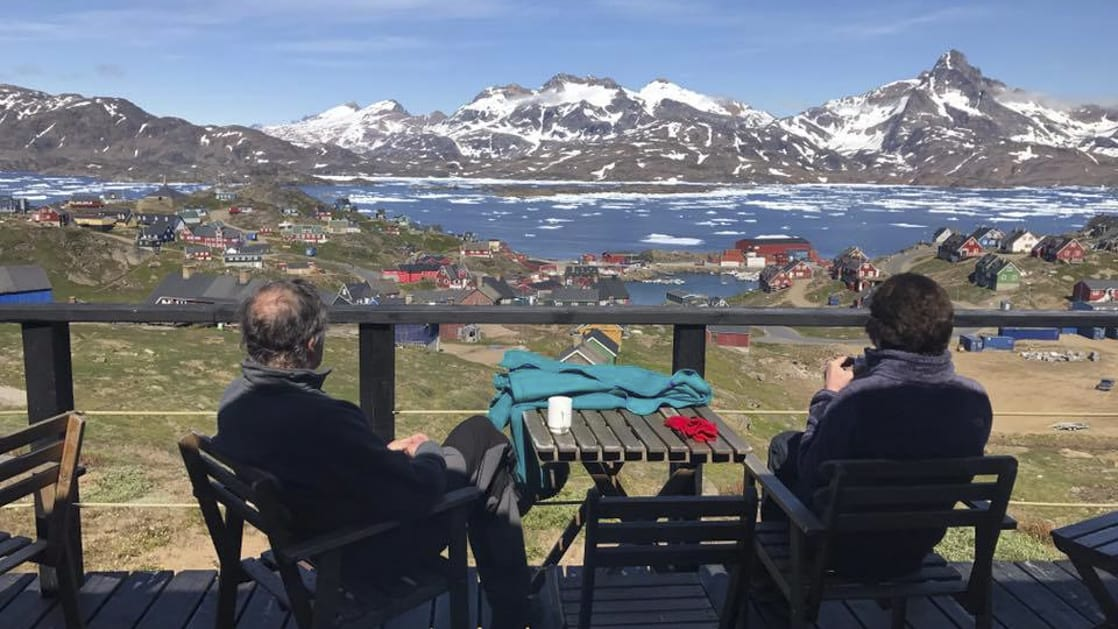 Two guests at the Hotel Kulusuk sit on the patio and take in views of Greenland's arctic waters and rocky mountain bluffs