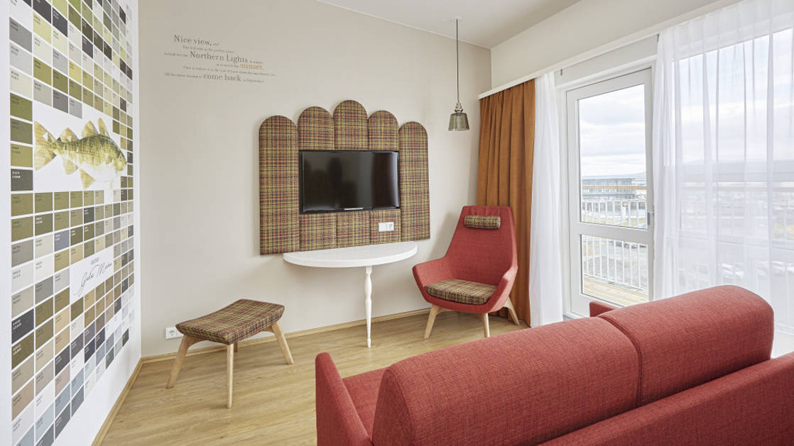 A different angle of the contemporary junior suite, with a flat-screen tv, couch, chairs, and large windows overlooking the harbor, at the the Icelandair Reykjavik Marina Hotel