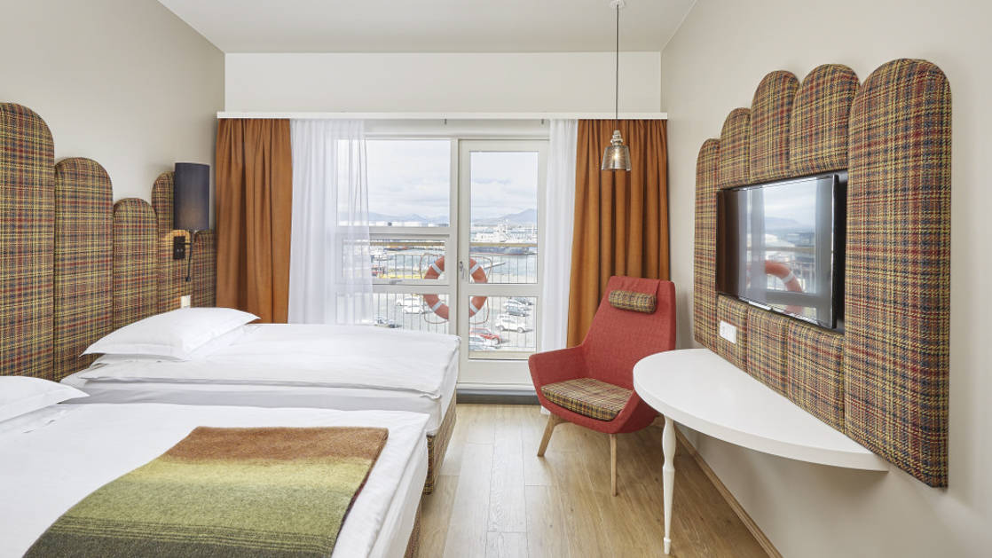 The twin deluxe room, with two full beds, a flat-screen tv and large windows overlooking the harbor, at the contemporary Icelandair Reykjavik Marina Hotel