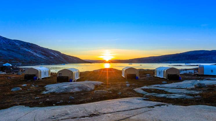 Sunset over the Sermilik Fjord, with the waterfront view of the cabins at Base Camp Greenland