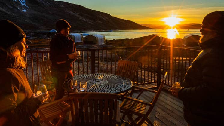 Three guests enjoy custom-made cocktails around an outdoor table while watching the sunset at Base Camp Greenland