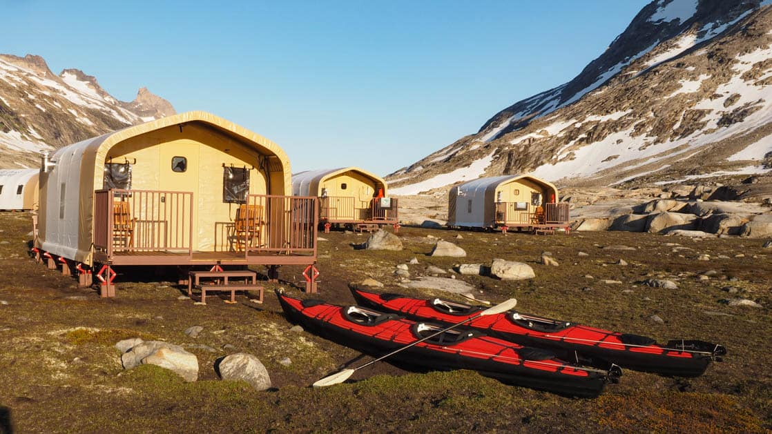 Safari-style tent cabins with two kayaks out front at Base Camp Greenland, in Sermilik Fjord