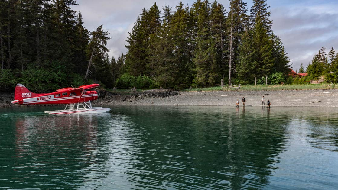 A float plane lands on calm water, next to a beach, with pine trees in the distance, at the Tutka Bay Wilderness Lodge near Homer, Alaska
