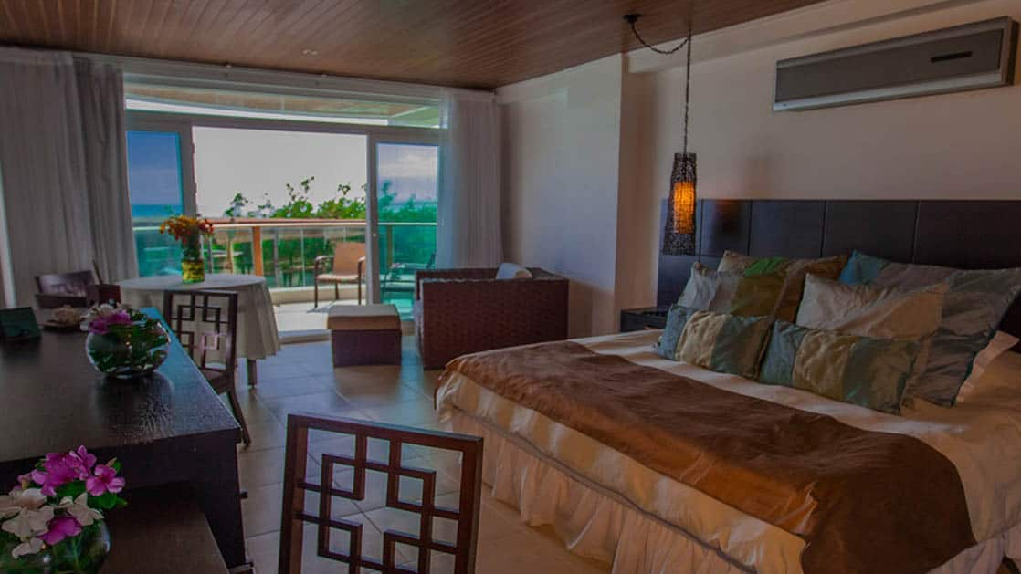 The spacious junior suite at Iguana Crossing Boutique Hotel with a king-sized bed, a ocean-front views, and and a private balcony overlooking the beachfront in Puerto Villamil on Isabela Island in the Galapagos