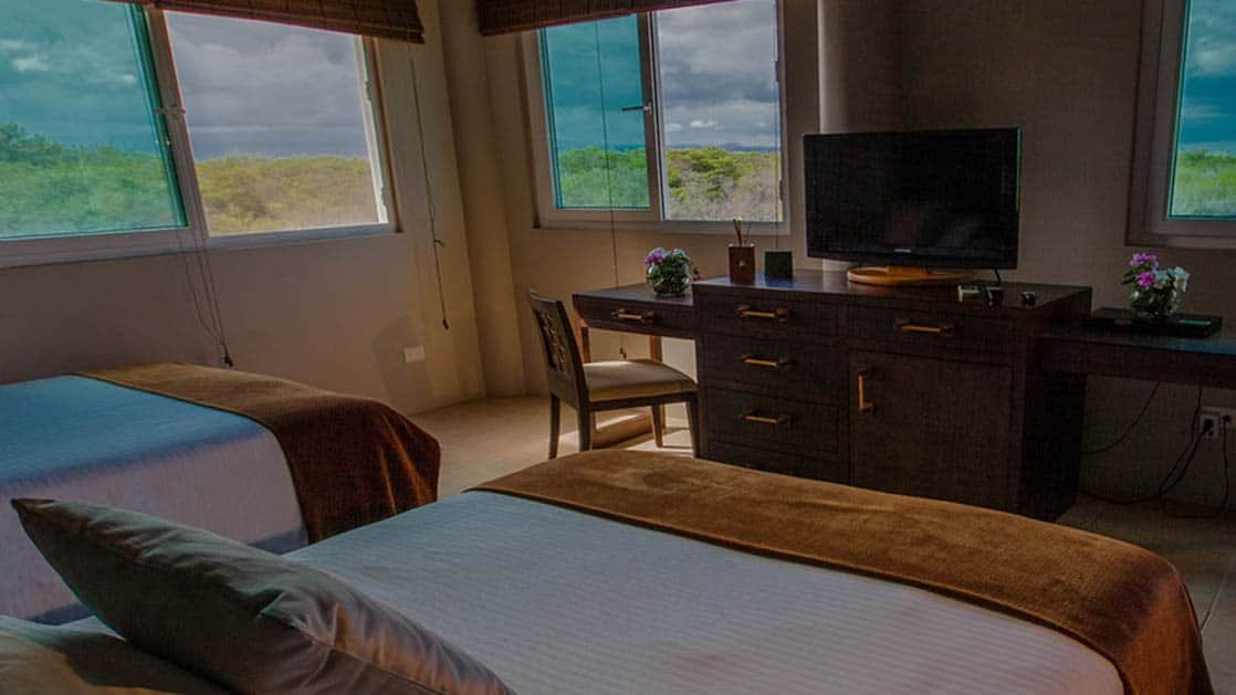 Two full beds in the Volcano View Room overlooks iconic landmarks like the scalesia forest and Sierra Negra at the Iguana Crossing Boutique Hotel, a sustainable eco resort in the Galapagos Islands