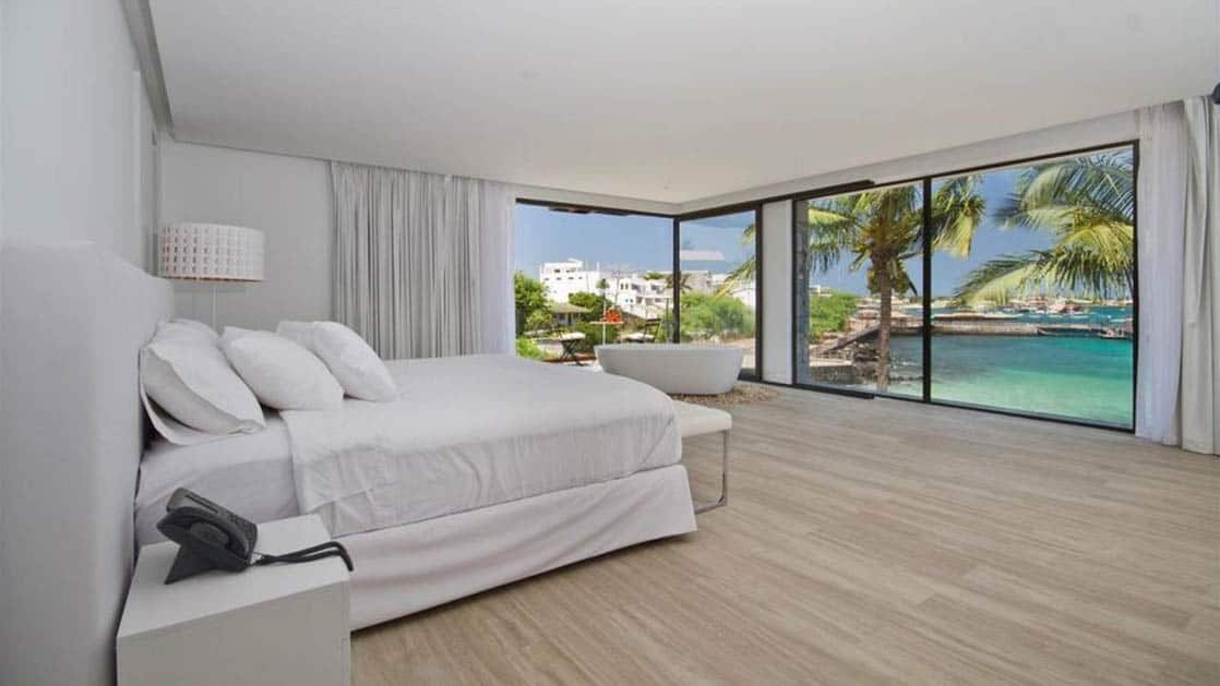 Suite interior with bed, bath, and ocean views at Golden Bay Hotel & Spa on San Cristobal in the Galapagos Islands