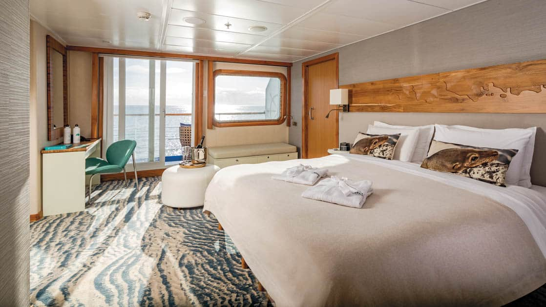 Large Balcony Suite Plus cabin on Galapagos Legend showing king bed, desk and colorful carpet