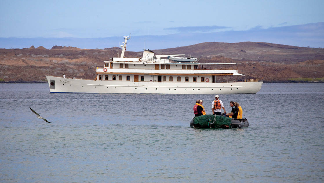 M/Y Grace anchored off the shore with a zodiac and crew members in front of the boat.