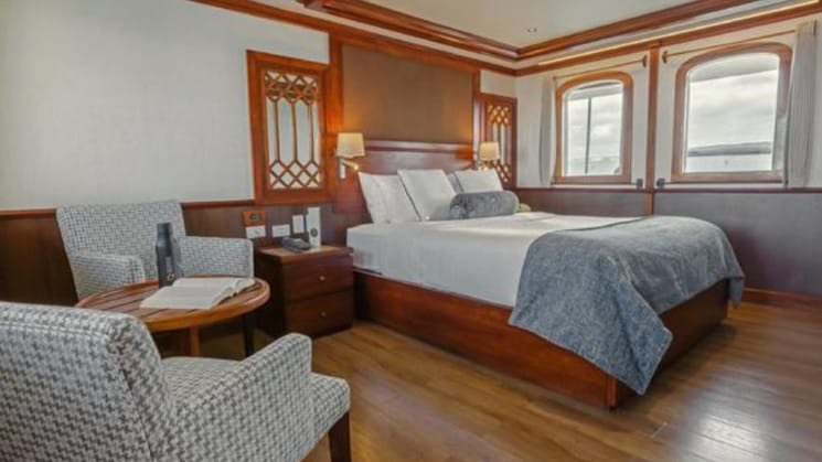 Grace master suite with large bed, seating area, table nightstands and 2 picture windows.