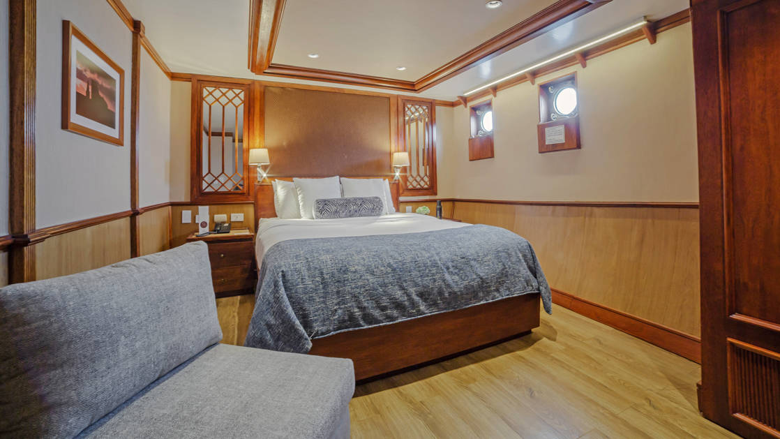 Grace stateroom with queen bed, chair and portholes.