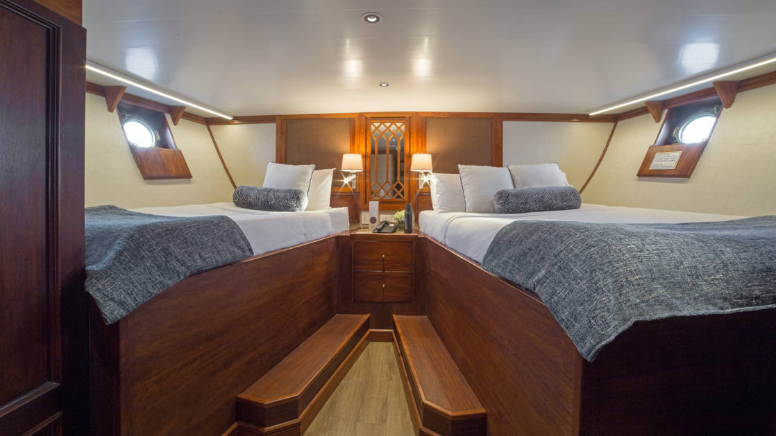 Grace stateroom with twin beds, nightstand and portholes.