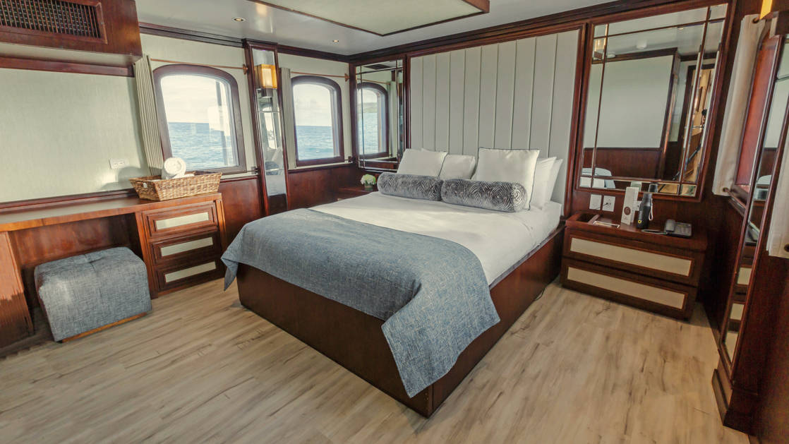 Grace suite with large bed, seating area, desk, dressers and large windows.