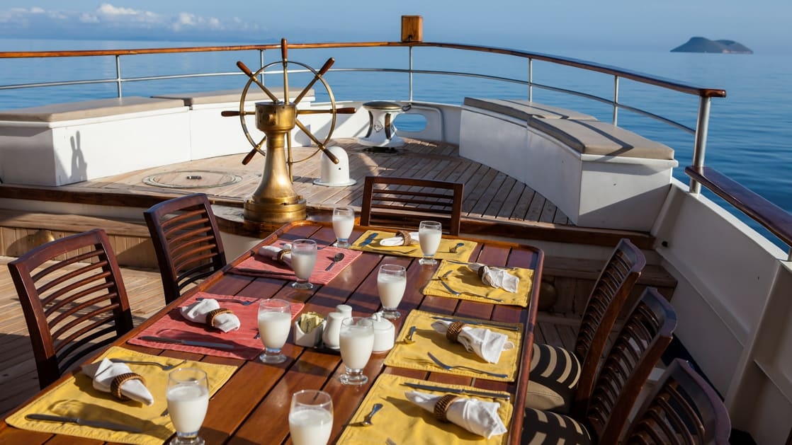 Grace outdoor deck next to the stern with a table and chairs set up for a meal outdoors.