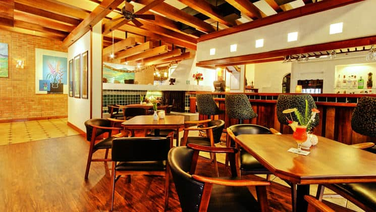 Bar with stools and nearby tables with chairs inside Hotel Bougainvillea near San Jose, Costa Rica