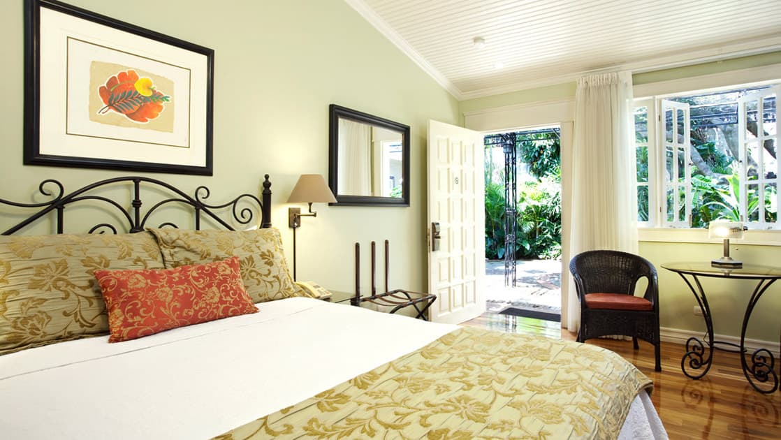 The superior room at Hotel Grano de Oro with a large, comfortable bed, fresh linens, and windows with a view of the jungle in Costa Rica
