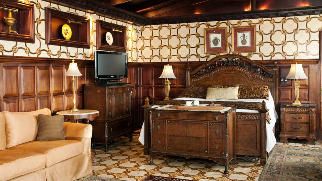 A suite at the Hotel Grano de Oro, decorated in traditional Costa Rican style and heritage, with a bed, a couch, decorative tiles and wood paneling