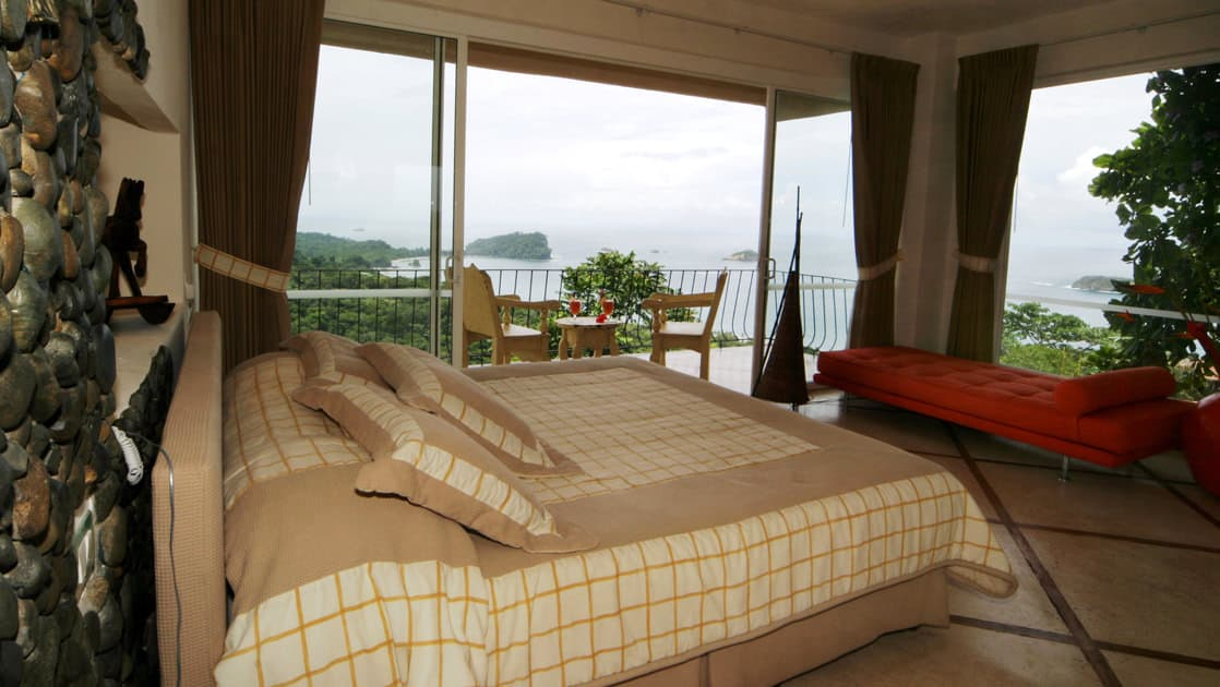 The Premier Ocean View Room at Hotel La Mariposa offers a panoramic vantage of the Pacific Ocean in Costa Rica with a king-sized bed and private balcony.