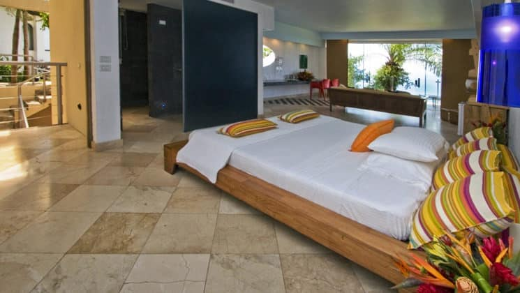 The Premier Room with a king-sized bed, private balcony, tiled floors, and modern decor at La Mariposa Hotel, one of Costa Rica's finest accommodations along the Pacific Ocean
